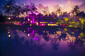 Abstract multiple-exposure view at dusk of palm trees and neon lights of Ocean Drive reflecting in puddle at dusk in South Beach, Miami, Florida, USA