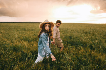 attractive stylish couple holding hands and walking on green meadow