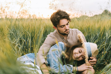 happy young couple embracing in green grass on meadow