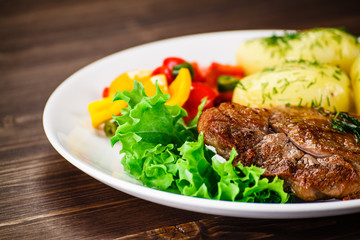 Grilled steak, baked potatoes and vegetable salad on wooden background