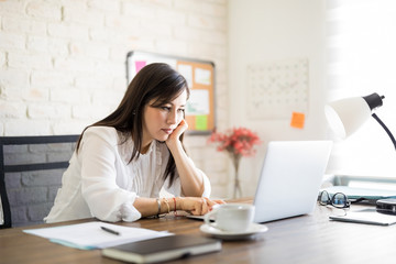 Bored woman working on laptop in office