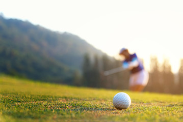 Golfer asian woman focus putting golf ball on the green golf on sun set evening time.  Healthy and Lifestyle Concept