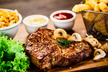 Grilled steak, French fries and vegetable salad