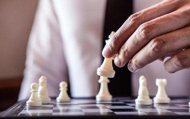 Hand of confident businessman use king chess piece white playing chess game to development analysis new strategy plan, business strategy for win and success