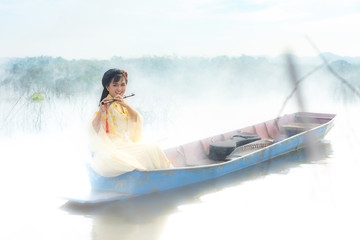 Chinese girl is playing the traditional Chinese musical instrument on the boats in the  lake ;Asia young woman play flute in the nature.