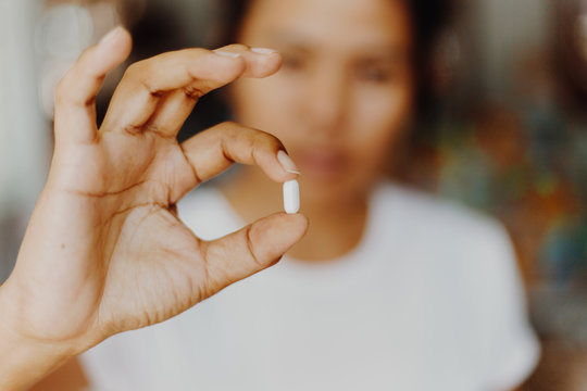 woman holding pills in one hand