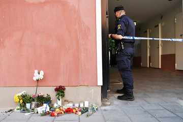 A police officer stands at a cordon, next to flowers and condolences outside the place where a 20 year old man with Down Syndrome, who was carrying a toy gun that was mistaken for a real gun, was shot and killed by the police, in Stockholm