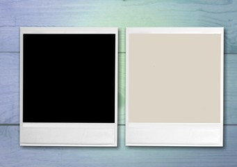 Blank retro photo frames on wooden background