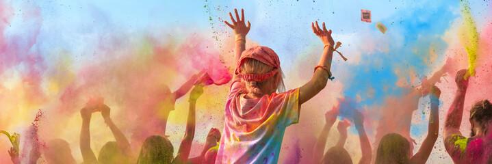 Breitbild - Holi Fest begeisterte Menschen jubeln auf einem Holifestival, tanzen und werfen mit buntem Holipulver