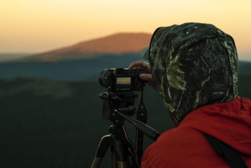 woman photographer takes a picture of a dawn in the mountains by camera on a tripod..