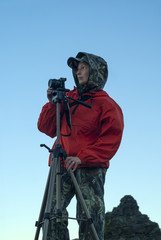 girl in hiking clothes looks into the distance, preparing to take a picture of the camera on a tripod