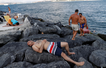 Men relax in the hot weather by the Marmara Sea in Istanbul