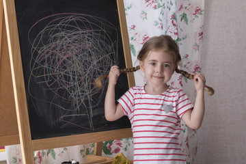 Child is drawing with pieces of color chalk on the chalk board. Girl is expressing creativity and looking at the camera. Concept of expression and learning