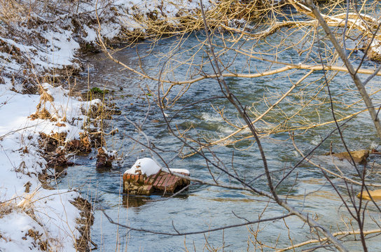 River flowing in winter with landscape of ground and tree covered in snow