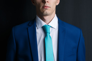 Close-up young man in an suit. He is in a white shirt with a tie. His face unshaven. Businessman in blue costume and turquoise necktie. Dark background.