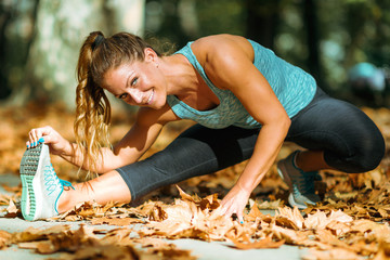 Woman stretching in the park, in the fall.
