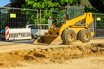 Orange dredger at a building site in the city. Construction of sewerage in the area. Parked work machines on the road. Bulldozer on site. Dropped road.