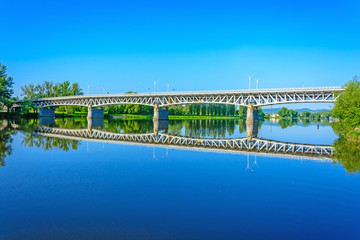 Steel bridge over the Labe river in Litomerice. The reflection of the bridge on the river. Sunrise on the River Elbe