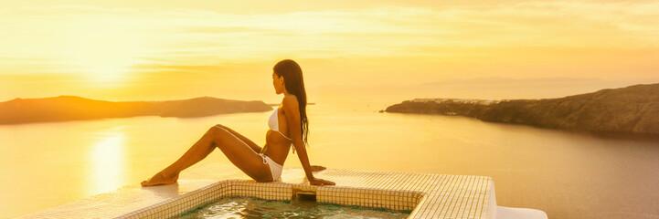 Wall Mural - Luxury travel Santorini hotel woman by resort swimming pool at sunset - Bikini body model sunbathing banner panorama.