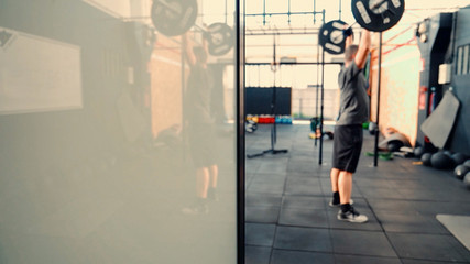 Man performing pull ups with heavy weights. Fitness exercise.