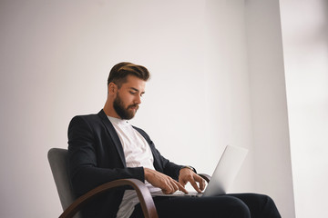 People, modern lifestyle, business and gadgets concept. Isolated shot of handsome young businessman with trimmed beard and stylish hairdo using generic laptop, communicating with partners online