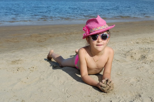 the child lies on a sandy beach in a pink hat and sunglasses.