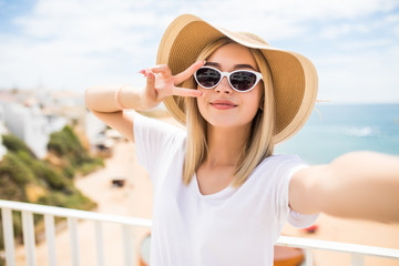 Close up of lovely young girl in summer hat taking a selfie and showing peace gesture at the beach