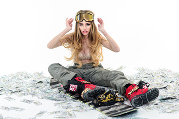 Snowboard girl. Winter leisure. Extreme sport. Attractive athletic woman in ski mask holds snowboard. Winter time. Ski mask. Snowboard girl in safety glasses siting on dollars. Sport concept. Money.