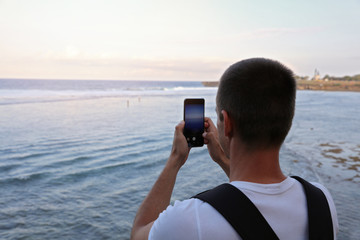 Man taking photo of sea cost with mobile phone. Summer, travel, adventure concept