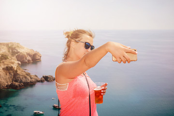 chubby girl with a glass of beer on a blue sea background takes a selfie on the phone.