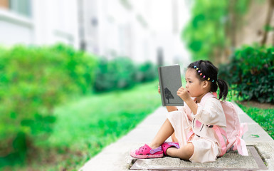 little girl reading a book with backpack sitting in the park ready back to school