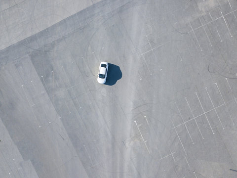top aerial abstract view of blue car running on asphalt with parking lots isolated copy space design