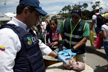Colombian immigration officers seize meat found in the luggage of a woman as she tries to cross into Colombia from Venezuela through Simon Bolivar international bridge in Cucuta