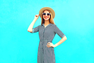 Fashion young smiling woman in striped dress on a blue background