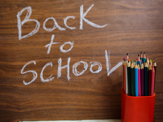 Coaster with pencils, yearbook and daybook, back to school text on the chalkboard