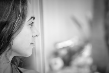 Black and white beautiful young woman looking out window on bright sunny day with copy space in window
