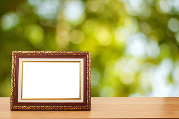 Photo frame on wooden table over abstract green bokeh background