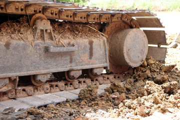 closeup Continuous tracks or Tracked wheel of excavator or backhoe on the soil floor. The aggressive treads of the tracks provide good traction in soft or hard surfaces. To be driven.