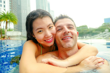 young happy and attractive playful couple taking selfie picture together with mobile phone at luxury urban hotel infinity pool enjoying holidays honeymoon