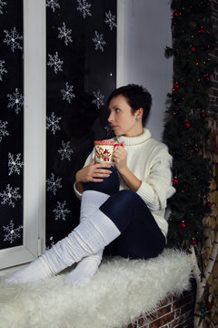 brunette girl in white sweater and white Golf in jeans sitting on a window with snowflakes wood and snowman concept new year in rustic style