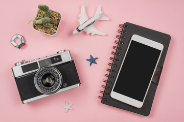 Retro camera with toy plane on pastel pink background with travel diary