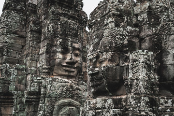 Faces of Bayon temple in Angkor Thom, The Bayon's most distinctive feature is the multitude of serene and smiling stone faces on the many towers