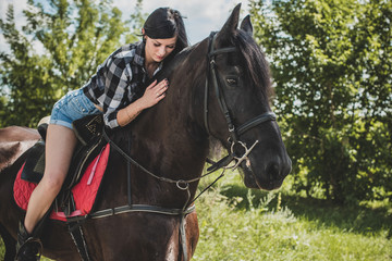 Woman enjoying horse company. Young Beautiful Woman dressed plaid shirt With black Horse Outdoors, stylish girl at american country style