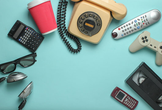 Retro objects on blue background. Rotary telephone, audio cassette, video cassette, gamepad,calculator, tv remote, headphones, push-button phone. Analog media technology of  past. Copy space..