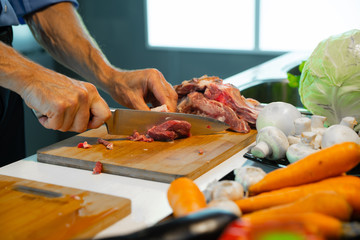 A man prepares food, cuts meat with a knife
