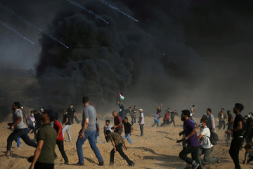 Tear gas canisters are fired by Israeli troops towards Palestinian demonstrators as they run during a protest demanding the right to return to their homeland at the Israel-Gaza border, in the southern Gaza Strip