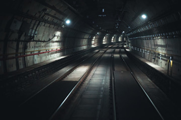 This is a front of view photo from the subway tunnel. It's composed by rails lights, concrete and cement
