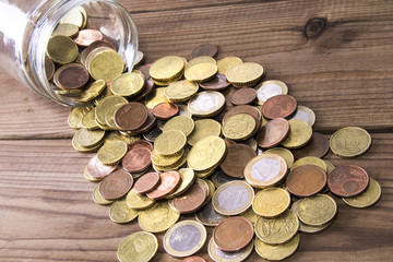 jar of coins scattered around the table