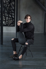Handsome young man with wet brown hair in all black outfit with crossed arms sitting on chair in a dark room