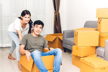 Happy couple having fun and moving man sitting in a cardboard box at home